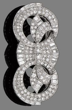 A diamond double-clip brooch, circa 1935. Each opposing openwork clip of circular and scrolling design, set throughout with old brilliant, brilliant and baguette-cut diamonds, diamonds approx. 7.20cts total, length 7.0cm.