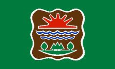 "Abenaki tribe flag.1991 the Abenaki Nation adopted a tribal flag. The flag has a dark green field recalling the Green Mountains and Vermont's ""green image"" with the tribal seal in the center. The brown ""shield"" of the seal represents deer or beaver hide. It features three symbols, with a red sun at the top. Below it a pair of blue waves denotes the rivers and Lake Champlain. A green grassy patch bears two deciduous and three conifer trees which stand for the lush woodlands of western…"
