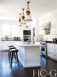White kitchen featuring Wolf appliances and bar stools from 2 Modern | Hamptons Cottages & Gardens