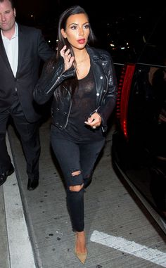 Kim flashes some cleavage in a sexy all-black outfit while making her way through LAX airport.