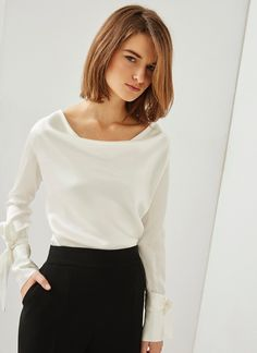 In a size 42. Long-sleeve blouse crafted in 100% Mulberry silk and presenting a distinguished cowl neckline. It has button cuffs, an elegant sheen, and removable bow embellishments on the forearms.