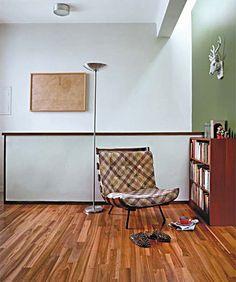 O piso da sala é de eucalipto reflorestado (Indusparquet). No alto da parede, um rasgo permite maior claridade, evitando o uso de luz artificial durante o dia. O anteparo em frente ao vidro evita o ofuscamento da visão. Projeto de Rodrigo Mindlin Loeb.