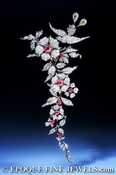 An important 19th century ruby and diamond branch brooch, designed as an articulated foliate spray surmounted by a bird of paradise, set with circular-cut and cushion shaped rubies, circular and rose cut diamons, pear-shaped peridots, mounted in silver and gold. Detaches into four brooches. English, circa 1880.