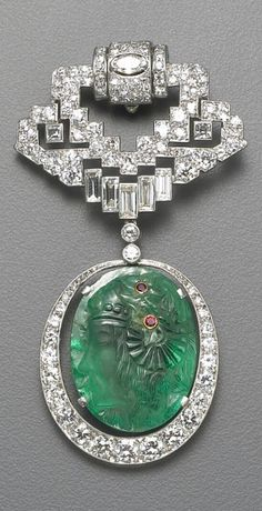 An art deco emerald, diamond and platinum clip brooch, French the openwork clip brooch of geometric design, set thoughout with old European and baguette-cut diamonds, suspending an articulated oval shaped diamond pendant centering an emerald carved with the profile of a woman accented by ruby collet detail; with French assay mark; estimated total diamond weight: 5.50 carats; length: 2¾in