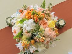 pastel centerpiece with peaches, oranges, yellows, pinks and creams