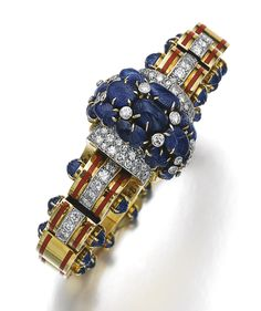 Sapphire, diamond, enamel and gold bangle, Jacques Lacloche, circa 1935 The front set with carved sapphires of leaf motifs, highlighted with circular-cut diamonds, the highly articulated band composed of gold segments, the sides accented with red enamel and carved sapphires, inner circumference approximately 140mm, expandable, signed J. Lacloche, French maker's mark