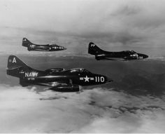 A pair of F9F-2B Panthers of Fighter Squadron (VF) 721 escort an F9F-2P Panther of Composite Squadron (VC) 61 during a mission over Korea on August 6, 1951. The aircraft operated off the carrier Boxer (CV 21).