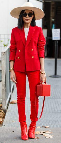 Un look classique : veste tailleur, slim et petite pochette relevé avec du rouge vif. Le tout assorti à un chapeau beige et des bijoux en or.