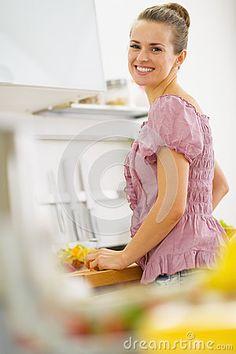 Porträt der lächelnden jungen Hausfrau in der Küche