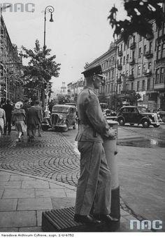 """Skrzyżowanie ulicy Marszałkowskiej i Złotej w kierunku alej Jerozolimskich.  Widoczny policjant regulujący ruchem, szyld kina """"Światowid"""" i samochody.  Źródło: NAC"""