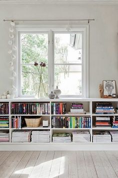 tiny house decorating and storage inspiration - low white bookshelves under a window. great for the living room.