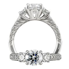Modern three stone diamond engagement ring featuring a prong set round cut center stone with two round cut side stones and a single row micropavé shank with cushion detail on the band profile.