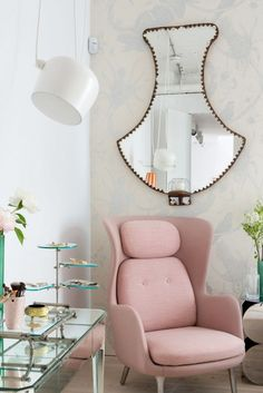Reading nook with midcentury pale pink lounge chair, uniquely-shaped mirror and modern lighting