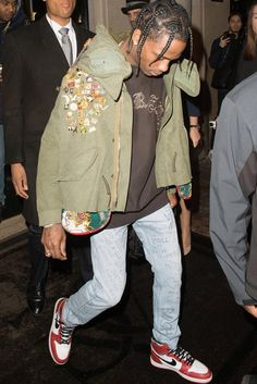 Travis Scott wearing Jordan 1985 1 Sneakers, Gucci Scribbled writing print punk pant, Supreme Vintage Script Sweatshirt, READYMADE Fishtail Parka