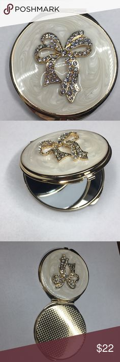 Enamel Rhinestone Compact Mirror Lovely pearl enameled compact mirror with crystal rhinestones set in a gold bow pattern. Double mirror compact for your makeup touch ups on the go. Very pretty comes new in box. Isabella Jewels Makeup Brushes & Tools