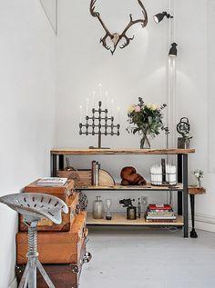 dekoracyjne walizki vintage,industrialny stołek i metalowo-drewniane półki w salonie