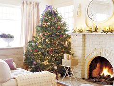 A beautiful collection of hand-blown glass balls—plain, faceted, and tinted—adorn this tree. Consider placing a tree near the fireplace so ornaments are illuminated by its light.   - CountryLiving.com