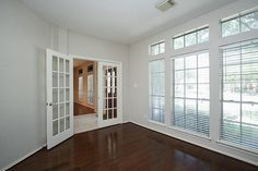 Double doors and a wall of windows in private study with wood floors. #FirstMarketRealty #BrokerJodi #HoustonRealEstate
