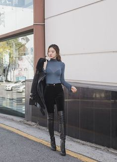 Asian girl in tight sweater thigh boots and leather jacket