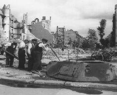 1945, Allemagne, Berlin, Des civils démontent une tourelle enterrée, après la fin de la guerre | by ww2gallery