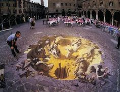 """This amazing street painting, called """"Dies Irae"""", was created by Kurt Wenner in a medieval town square in Italy. Again, note that it is an anamorphic image - it only works from this viewpoint. If you walked around to the other side of the painting, it just would not work at all. Here, the human figure gives a sense of scale, as he peers into the abyss."""