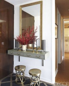 A custom wall-mounted console covered in a shagreen by Edelman Leather and a vintage mirror in the entry hall; the flooring is original.