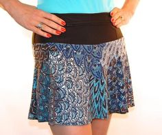 """As subtle as a morning mist, this lightweight blue peacock athletic skirt has soft shades of blues with light blue sequins. Standard black wicking anti-ride undershorts hold two 5x5"""" pockets and the r"""
