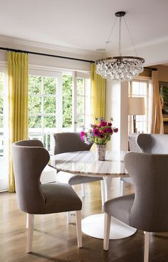 Molly Sims - Fabulous dining room features an Ochre Arctic Pear Chandelier hanging over a Saarinen Dining Table lined with gray wingback dining chairs accented with silver nailhead trim placed in front of windows dressed in yellow curtains.