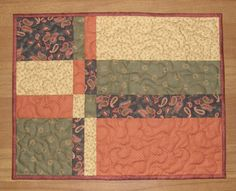 These fall quilted placemats feature four earth tone fabrics that will remind you of crisp colorful leaves, bon fires, and cooler weather. The four fabrics I used in these unique placemats are rusty orange, olive green, barn red paisley set on a soft black, and buttery gold. A perfect addition to your harvest table or on end tables to add a touch of color. A wonderful accent to your current fall decor or use the placemats all year long. 18 1/2 x 14 1/2  Set of 4  100% quilt shop qua...