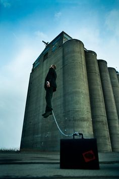 Suggestion that businessman is chained to work - enhanced by industrial theme/setting