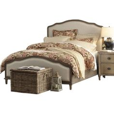 Pairing a curved wood frame and cream-hued upholstery, this elegant bed makes a lovely canvas for a bold floral comforter or country-chic quilt.