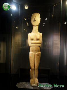 Esta impresionante pieza (altura 1,40 m), que puede clasificarse justificadamente como una estatua, se distingue por contornos claros, proporciones perfectas y plasticidad de formas. El movimiento latente, indicado por la cadera izquierda superior y el hombro correspondiente y que culmina en la ligera inclinación de la cabeza hacia la derecha, infunde a la figura con un aire de misterio, estableciéndola como el precursor distante de las esculturas monumentales de los tiempos arcaicos.