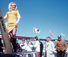 "A very young Linda Vaughn struts her stuff as Miss Hurst Golden Shifter at Daytona in the early '70s.  Look at the lady in the sunglasses and then the young man in the trench coat.  They obviously have differing opinions about Linda.  Today Linda is known as ""The First Lady of Motorsport"" and for obvious reasons."