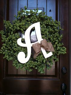 Love the way a bright white letter stands out.  What a simple, pretty wreath for a dark door.