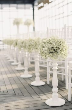 Line your aisle with baby's breath in striking white pedestals like these for a lavish ceremony look.    Image via  Weddings Romantique.
