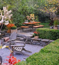 Separating Spaces..multi level yard with steps to a gravel fire pit down + steps to a eating area and garden up.