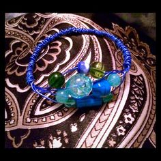 Flex wire bangle w/ sea glass like & wooden beads. Wrapped, flexible, wire bangle. Blue wire & blue & green beads. Glass, acrylic & wooden beads to create a sea glass look.  Handmade!   By Kiwi Kissed Designs.  I use found items, buy single items & small quantities so that your purchase is unique.  Items cannot be replicated exactly due to this, but I can make similar items if a particular item is no longer available.  Request welcome! Jewelry Bracelets