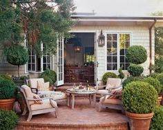 brick patio. Love the box woods, patio furniture, pained glass, and lanterns