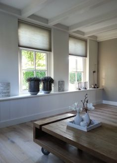 mooie houten vloer, brede vensterbank en duette gordijn.