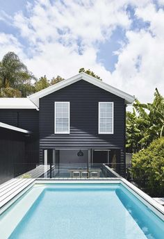 Exterior: The stark white window trim and roof contrast beautifully against the dark exterior of the pool house. The exterior painted is in 'Weathershield' in Black and Casper White Quarter from Dulux.
