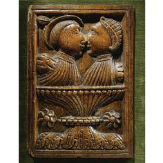 A rare English carved oak panel third quarter 16th century depicting a couple face to face above a gadrooned vessel or chalice and twin flower head motifs within a moulded surround, on a later velvet lined mount