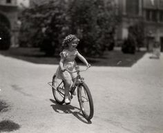 Shirley Temple rides a bike.