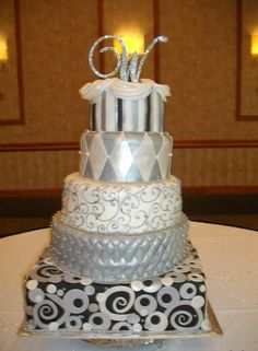 Another cake with different layers.  Some fondant work looks slightly sloppy, but good overall concept.  Like it in the silver, but don't know if that'd go with the theme.