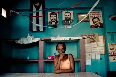 A Cuban woman stands behind the shop counter, holding a flower, in front of a wall covered by photos of the Cuban Revolutionary leaders, Santiago de Cuba, Cuba.