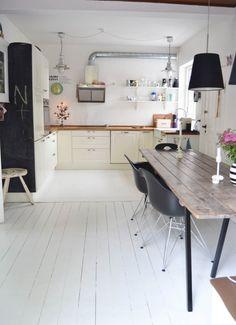 las paredes y el suelo blancos, sumados a los tubos metálicos al aire y la mesa de madera reciclada, consiguen el efecto deseado