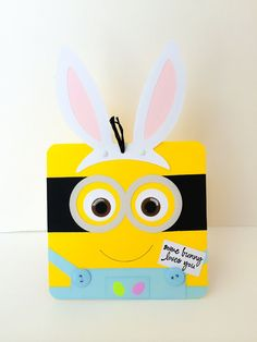 Handmade Minion Easter card for kids. Perfect Easter greeting for kids or minion fans. Minion has button overalls with Easter eggs on the pocket.