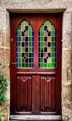 Wood door with stained glass windows in Parthenay, Deux-Sèvres, France.