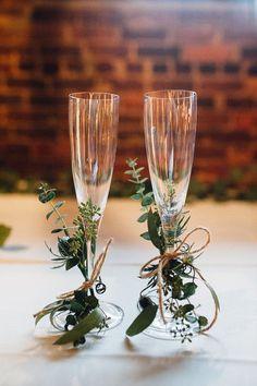 Flautas de champagne vestidas con ramas de eucalipto e hilo sisal o torzal. Una manera muy sencilla para decorar tus copas de novios. Fotografía: Cameron Reynolds Photography