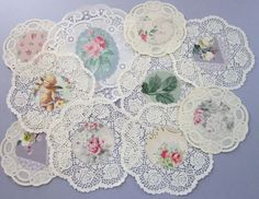 Lot of (10) vintage paper lace doilies, embellished with vintage wallpaper centers (c1940s) .. including roses, floral, cherub. A variety of designs, shades of white and cream, and sizes.