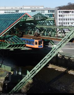 A train from the 'Suspension-railway' leaves the station Kluse/Schauspielhaus with the special stationbuilding. There is only one line with 20 stations, the cabin is hanging at the track. Orange and blue are the original colors. The trains run mostly above the river 'Wupper'